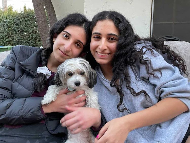 Shira Berukhim, 9th grader (left) and Yael Berukhim, 12th grader (right) Belle (dog in the middle)